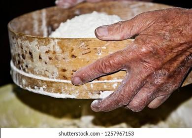 Grandma's old wrinkled hands sift flour