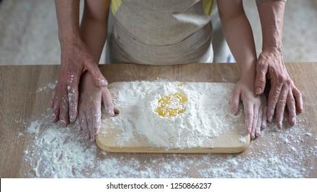 Grandmom carefully teaching granddaughter kneading dough, family recipe, cooking