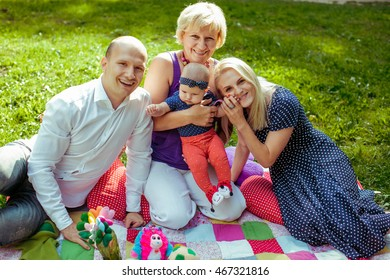 Grandmom holds a little girl while her parents sit around her