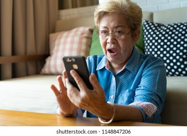 Grandmom is playing social media via her mobile phone and feeling surprise something on the cell phone.