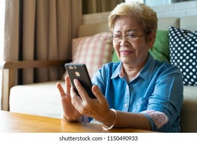 Grandmom is playing social media via her mobile phone.