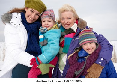 Grandmother with adult daughter and granddaughters on winter day smiling at camera