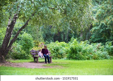 Grandmother and baby girl relaxing in a park on a bench under a big beautiful tree on a warm autumn day