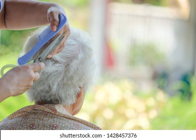 the grandmother is being a haircut in nature