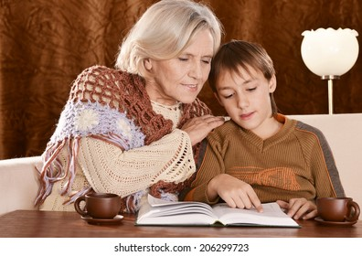 Grandmother and boy read together at home on sofa