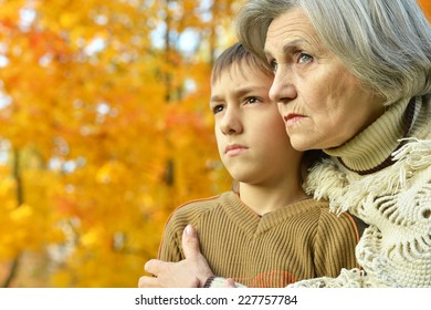 Grandmother with boy resting in autumn park