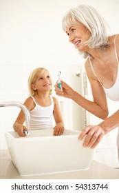 Grandmother Brushing Teeth In Bathroom With Granddaughter Watching