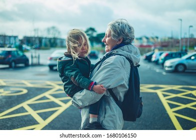 A grandmother is carrying her preschooler grandchild in a parking lot