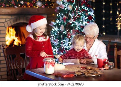 Grandmother and children baking Christmas cookies at fire place and Xmas tree. Kids and grandma bake sweets. Family with kids celebrating Christmas at home. Boy and girl cooking. Generations love
