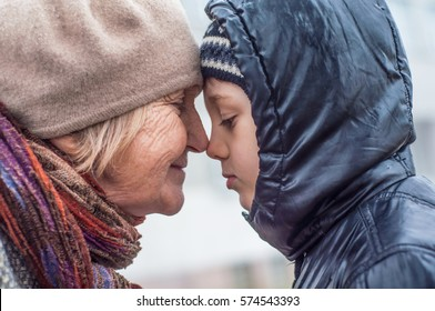 Grandmother comforts her grandson. The older woman and a boy in profile close-up
