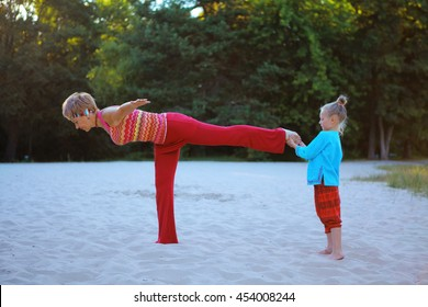 Grandmother and daughter practicing yoga at sandy beach outdoor at the magic rays of sun light. Healthy lifestyle. Family sport lessons and workout for all ages. Warrior Pose or Virabhadra balance