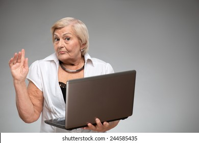 Grandmother in the Digital age. Closeup of thoughtful senior woman trying to cope with computer while standing against grey background