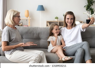 Grandmother displeased by mother with preschool daughter making selfie, mobile device addiction concept, different age generation conflict, parent using mobile phone with child together at home