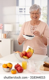 Grandmother eating blueberry, having many fruits on kitchen counter, smiling happy.