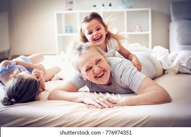 Grandmother enjoying in bed with her little granddaughters.