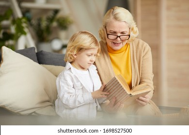Grandmother in eyeglasses reading a book to her son during their leisure time at home