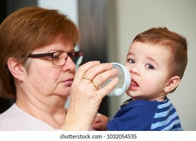 Grandmother feeding baby grandson with milk from nursing bottle