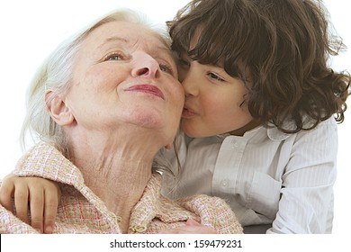 Grandmother getting a kiss from grandson. Isolated on white background.