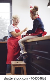 Grandmother with girl cooking and enjoying