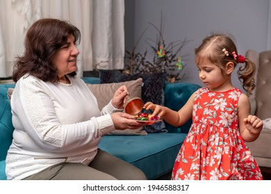 Grandmother give to her cute little granddaughter candies during Ramadan feast (aka: Ramazan or Seker bayrami). Sweets in little child girl  hands as a tradition in middle eastern culture. Real people