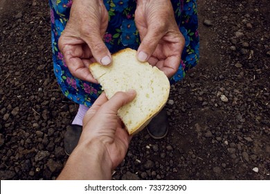 Grandmother gives bread to her granddaughter