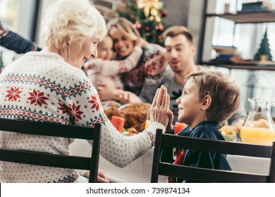 grandmother giving high five to grandson while celebrating christmas with blurred family on background