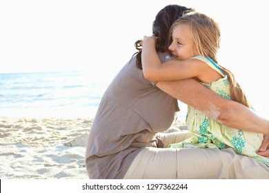 Grandmother and grand daughter enjoying sunny beach holiday hugging, heads together, joyful smiling with sunny sky, outdoors. Senior and child playful fun bonding family travel activities lifestyle.