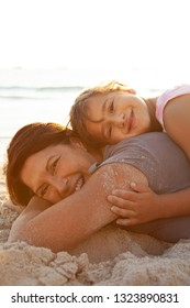 Grandmother and grand daughter laying on sand, heads together, enjoying sunset beach holiday, joyful looking, smiling hugging outdoors. Senior and child fun bonding family travel activities lifestyle.