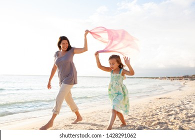 Grandmother and grand daughter walking together on beach holding floating fabric by the sea, outdoors. Family childhood activities, joyful games leisure recreation lifestyle, fun summer lifestyle.