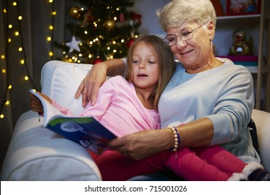 Grandmother and grandaughter in armchair with book