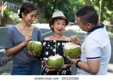 Grandmother and grandchildren enjoying fresh coconut juice on the roadside. Summer outdoor picture.