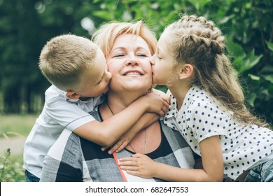 Grandmother with grandchildren hugging in the park