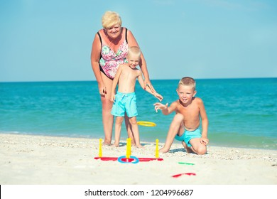 Grandmother with grandchildren playing a game throwing rings on the beach.