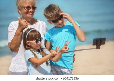 Grandmother with grandchildren taking selfie.