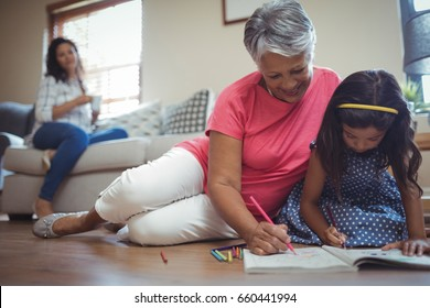 Grandmother and granddaughter coloring book in living room at home