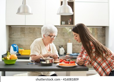 Grandmother with granddaughter cooking in the kitchen.