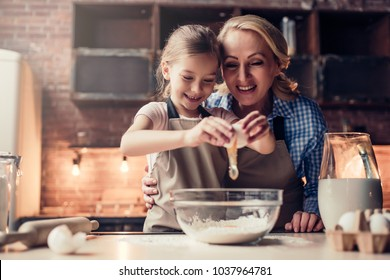 Grandmother and granddaughter are cooking on kitchen. Making tasty baking together.