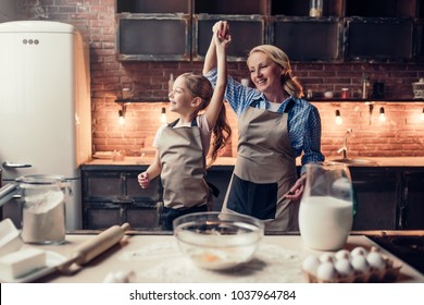Grandmother and granddaughter are cooking on kitchen. Making tasty baking together. Dancing and having fun together.