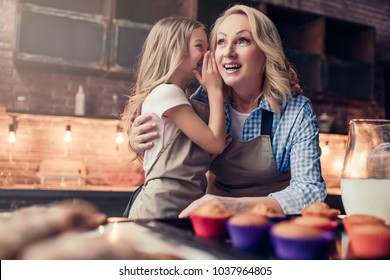Grandmother and granddaughter are cooking on kitchen. Making tasty baking together. Little girl is whispering the secret to grandma's ear.