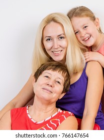 grandmother with granddaughter and daughter hugging and laughing