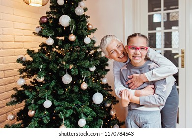 Grandmother and granddaughter decorating a Christmas tree