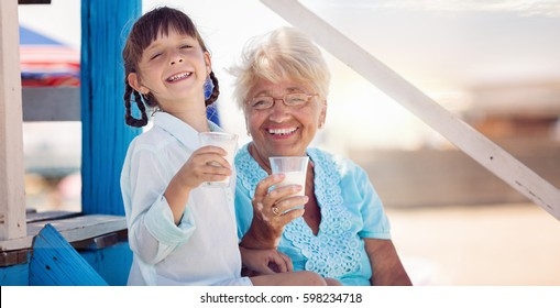 Grandmother with granddaughter drinking milk outdoors.