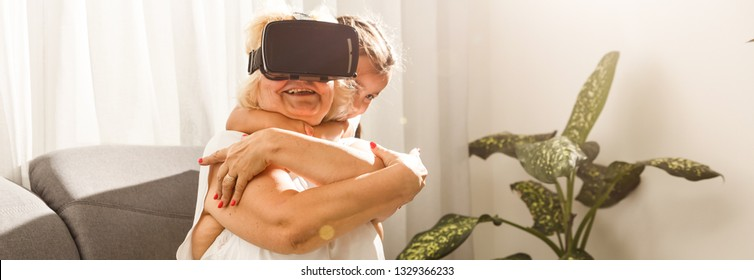 c24b39376f0d grandmother and granddaughter. Happy old woman playing virtual reality with  little girl at home.