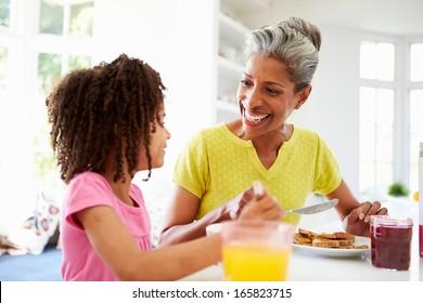 Grandmother And Granddaughter Having Breakfast Together
