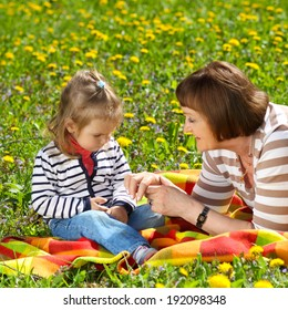 Grandmother and granddaughter having fun on a blanket on a background of yellow flower meadows. Naughty beautiful little baby with her grandmother outdoors. Grandmother and grandchild