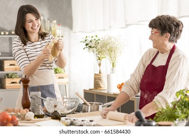 Grandmother and granddaughter having fun while cooking together
