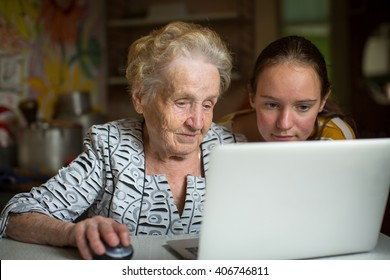 Grandmother and granddaughter learn to work on computer.