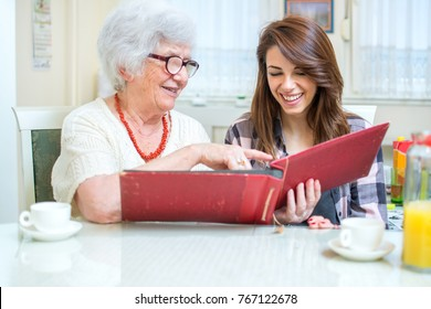 Grandmother and granddaughter looking at photo album.