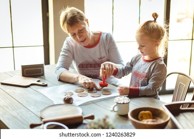 Grandmother and granddaughter in the morning in the same pajamas together bake Christmas cookies-stamps on the test. The family cozy Christmas concept. Selective focus.