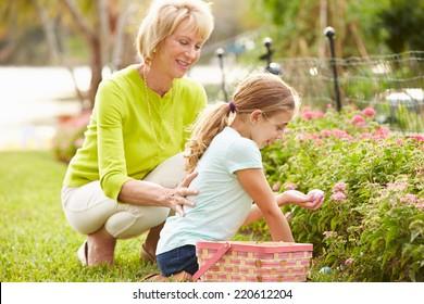 Grandmother With Granddaughter On Easter Egg Hunt In Garden